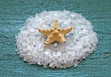 Seesalz mit Starfish auf hölzernem Hintergrund Lizenzfreie Stockfotografie
