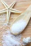 Seesalzkristalle im hölzernen Löffel auf hölzernem Hintergrund Lizenzfreies Stockfoto
