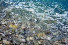 Seesalzwelle, Wasser bedeckt die Küstenkiesel, Steine Lizenzfreies Stockfoto