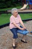 Seesaw Grandma. Senior citizen woman on a playground seesaw stock photography
