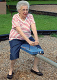 Seesaw Grandma 3. Senior citizen woman on a playground seesaw royalty free stock photography