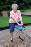 Seesaw Grandma 4. Senior citizen woman on playground seesaw royalty free stock photo