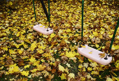 Seesaw on the playground covered with autumn leaves Royalty Free Stock Images