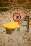 Seesaw. In a playground with scattered autumn leaves Stock Photo