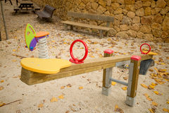 Seesaw. In a playground with scattered autumn leaves Stock Images