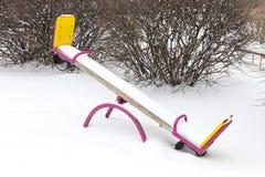 Seesaw ` s детей покрытый в снеге и на спортивной площадке в зиме Стоковая Фотография