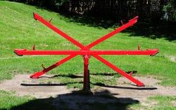 Seesaw symmetry. Striking red seesaw symmetrically arranged Royalty Free Stock Photo