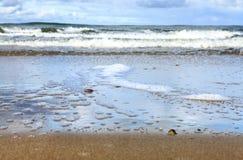 Seeschaum, der das sandige Ufer wäscht Stockbild