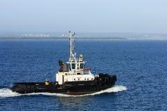 Seeschlepper unter Leistung im Hafen. Stockfotos