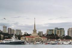Seestation, -boote und -yachten im Hafenwasserstand gegen den Hintergrund von Stadthöhen an einem bewölkten Frühlingsabend lizenzfreie stockfotografie