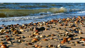 Seesteine im Sand, in der Seeküste mit Steinen und im Sand Stockbilder