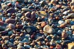 Seesteine im Sand, in der Seeküste mit Steinen und im Sand Lizenzfreie Stockfotos