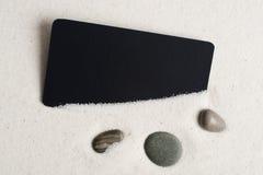 Seesteine und schwarzes Schnitt auf Sand. Stockfotografie