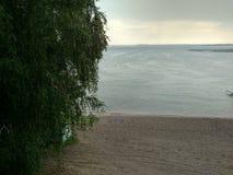 Seestrand an einem regnerischen Tag mit einer Wolldecke, die die Ansicht des Horizont Suppengrüns mit Blattmakrotropfen der Ansic stockbild