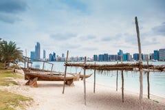 Seestrand mit altem hölzernem boath und Luxus skyscarper Lizenzfreie Stockfotos
