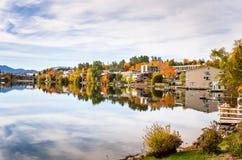 Seeufer-Dorf im Herbst und in der Reflexion im Wasser Lizenzfreies Stockbild