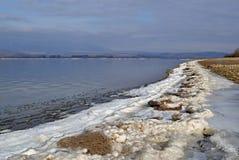 Seeufer mit einem Streifen des Schnees und des Eises Lizenzfreies Stockfoto