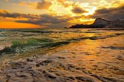 Seewelle auf dem Strand, die Brandung auf der Küste Schwarzen Meers bei Sonnenuntergang Stockfotografie