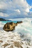 Seewelle, die auf einem großen Felsen bricht Lizenzfreie Stockfotografie