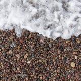 Seewelle und nasse Steine Stockfoto