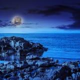 Seewellenbrecher über Flusssteine nachts Stockbilder
