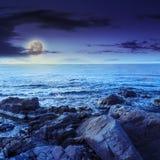 Seewellenbrecher über Flusssteine nachts Stockbild