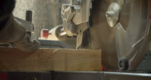 Sega per tagli trasversali del colpo del primo piano che scolpisce il legno nei piccoli quadrati alla fabbricazione video d archivio