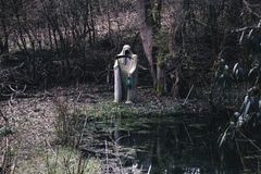 Segador blanco de la muerte con la guadaña y la lámpara fantasmagóricas en una pequeña charca fotografía de archivo