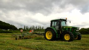 A segadora grande está girando acima da grama seca, caminhão com o fabricante do feno que trabalha no prado na terra video estoque