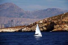 Segelbåt över kusten av den Benidorm staden i Spanien Arkivfoton