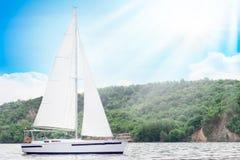 Segelbåt i havet i sunntdagen över härlig stor bergbakgrund, lyxigt sommaraffärsföretag, aktiv semester Utrymme för arkivbilder