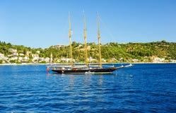 Segelbåt i ront av havskusten och den blåa himlen Arkivbilder
