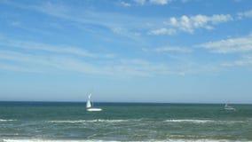 Segelbåt i vädret för hav utom fara, på himmel med bakgrund för några vit moln Segla yachten i det blåa havet nära kusten arkivfilmer