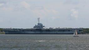 Segelbåt längs sida den USS Yorktown hangarfartyget royaltyfria bilder