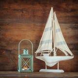 Segelbåt och lykta för gammal tappning trävit på trätabellen tappning filtrerad bild nautiskt livsstilbegrepp Royaltyfri Bild