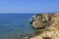 Segelbåt på den öde stranden och klippor arkivbild