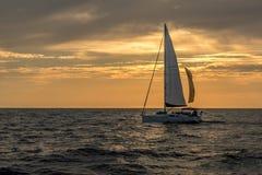 Segelbåt på det öppna havet under solnedgång under molniga himlar Arkivbilder