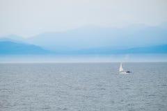 Segelbåt på havet med bakgrund för dimmigt berg Royaltyfri Foto