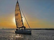 Segelbåt på solnedgångöverskriften in i södra tillflyktsorthamn Fotografering för Bildbyråer