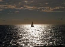 Segelbåt på solnedgång Arkivbild