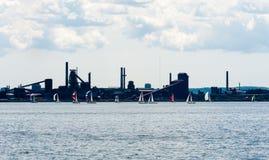 Segelbåtar förbigår industriområde i Hamilton, Ontario, Kanada Arkivbilder