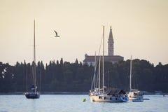 Segelbåtar framme av den helgonEufemia kyrkan Arkivbild