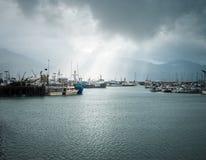 Segelbåtar i hamnen med solen rays kommande down från en stormig Seward himmel arkivfoto