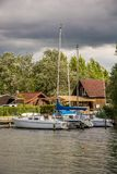 Segelbåtar ligger på en brygga med ett härligt trähus i bakgrunden royaltyfri fotografi