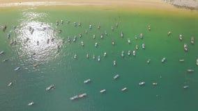 Segelbåtar och fiske sänder i det blåa havet nära flyg- landskap för sandig kust Fiskebåtar och seglingskepp i havet stock video