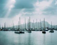 Segelbåtar och nöjefartyg i porto den stora fjärden av den historiska staden Mindelo Clodscape med solstrålar Royaltyfri Fotografi