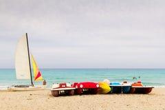 Segelbåtar och paddleboats på en karibisk strand Royaltyfri Fotografi