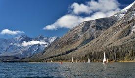 Segelbåtar på lägre kananaskis sjö i nedgången efter en ny snö Arkivfoto