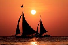 Segelbåtar på solnedgången royaltyfria bilder