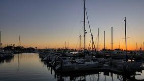 Segelbåtar som tjudras på Marina Dock på solnedgången i San Diego California arkivfoto